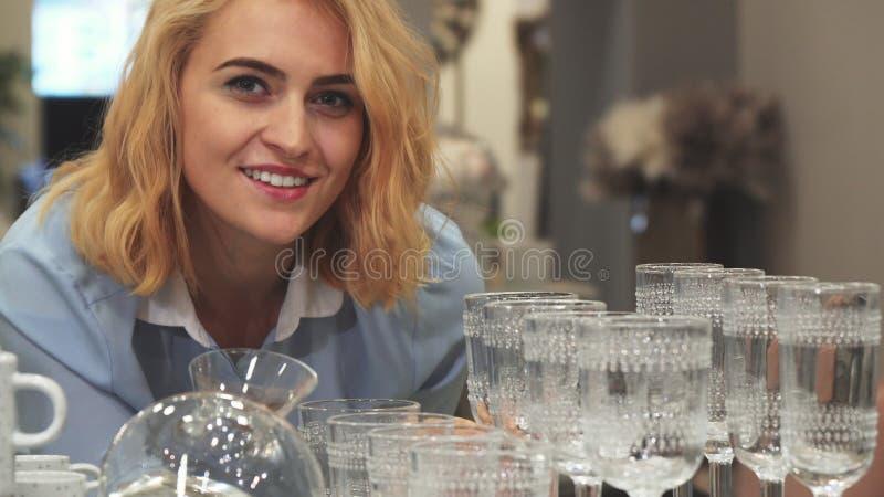 Het meisje kiest nieuwe wijnglazen voor huis stock afbeelding