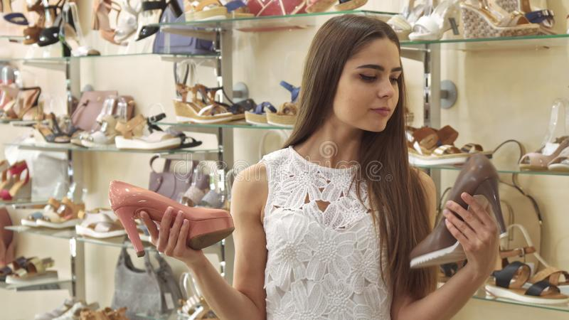Het meisje kiest tussen perzik en bruine schoenen royalty-vrije stock foto