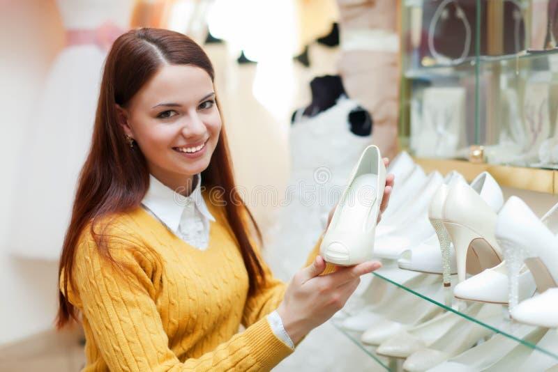 Het meisje kiest witte schoenen in boutique stock foto's