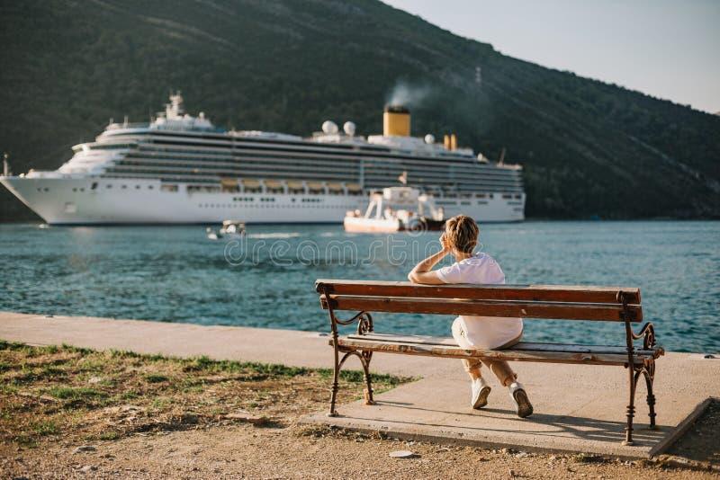 Het meisje kijkt de cruise van de de bankvoering van de schipzitting royalty-vrije stock afbeelding