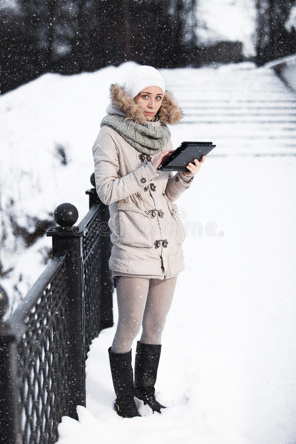 Het meisje kijkt in de tabletcomputer in een de winterpark Er is stock afbeeldingen