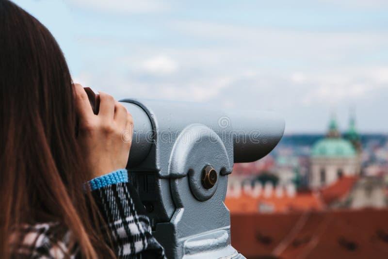 Het meisje kijkt door de verrekijkers op de mooie architectuur van Praag op de observatieplaats Praag is één van royalty-vrije stock afbeeldingen