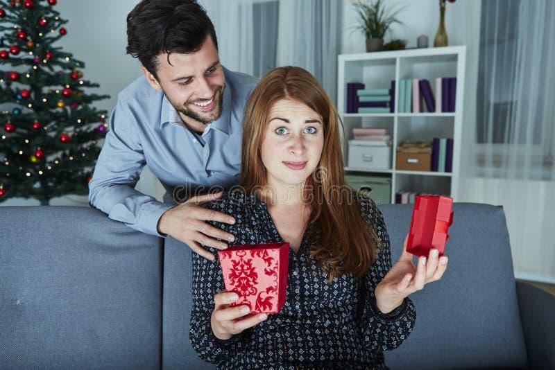 Het meisje kijkt sceptisch aan haar Kerstmisgift royalty-vrije stock fotografie