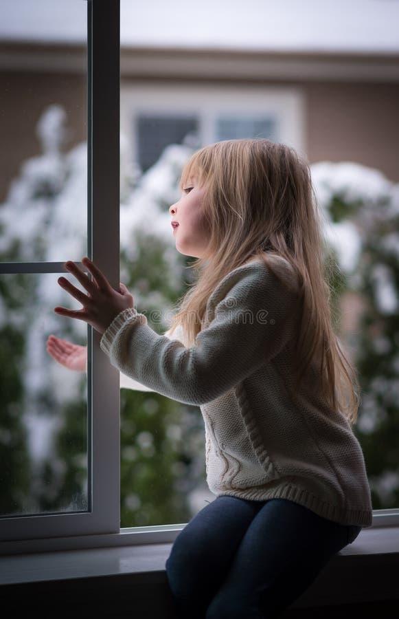 Het meisje kijkt uit het venster. royalty-vrije stock afbeeldingen