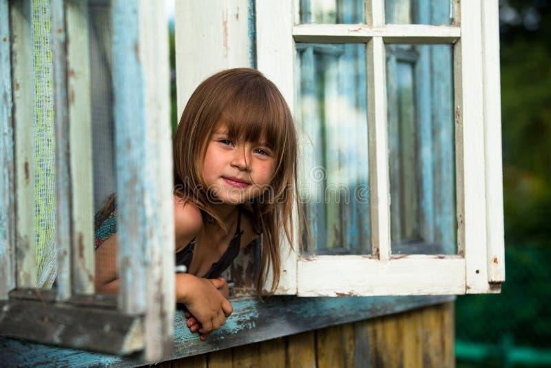 Het meisje kijkt uit het venster landelijke huis royalty-vrije stock fotografie