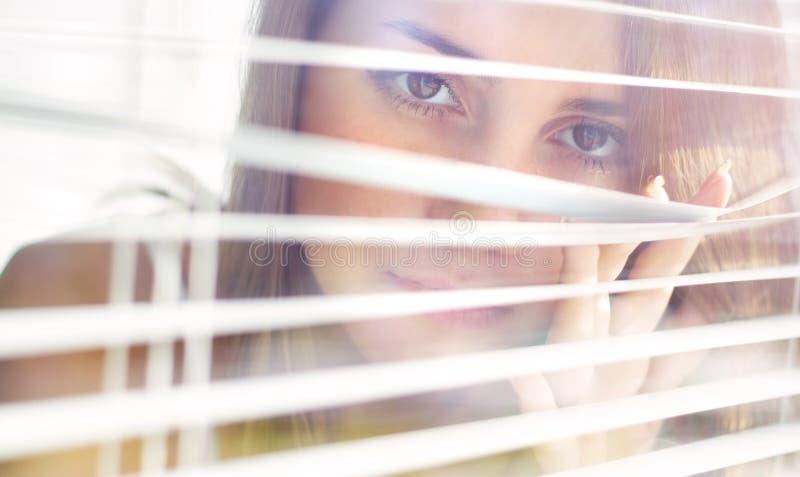 Het meisje kijkt uit zonneblinden royalty-vrije stock fotografie