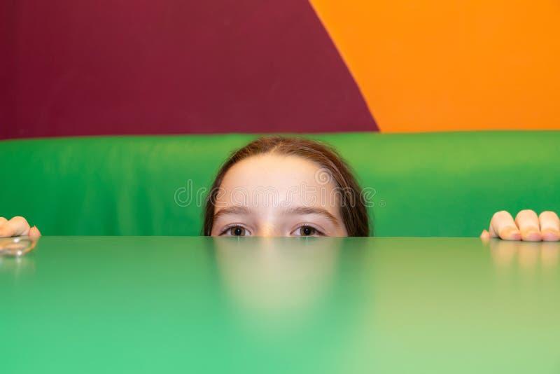 Het meisje kijkt van de lijst stock fotografie