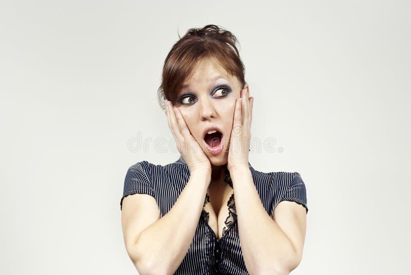 Het meisje kijkt verrast op een grijze achtergrond stock fotografie