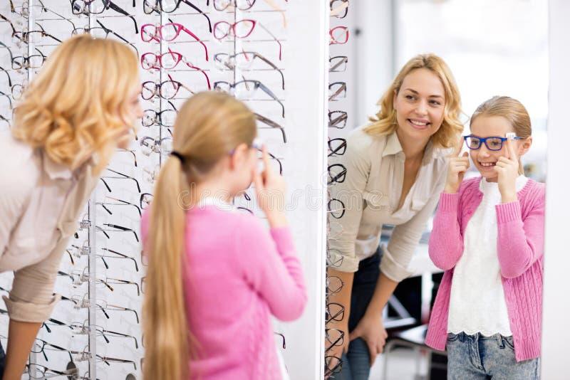 Het meisje kijkt zelf in de spiegel met nieuwe oogglazen stock afbeelding