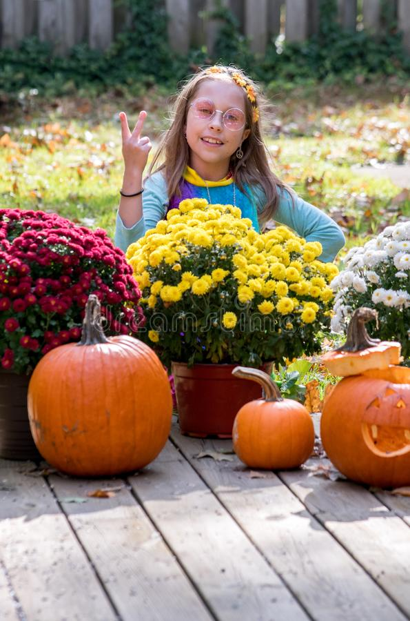 het meisje kleedde zich als kind van de hippiebloem, flitsen een vredesteken stock foto's