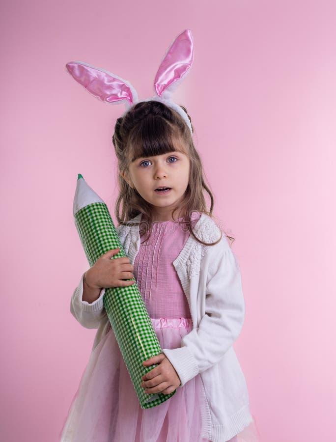 Het meisje kleedde zich als Paashaas die zich op witte achtergrond bevinden en potlood houden De Vakantieconcept van kindpasen stock foto's