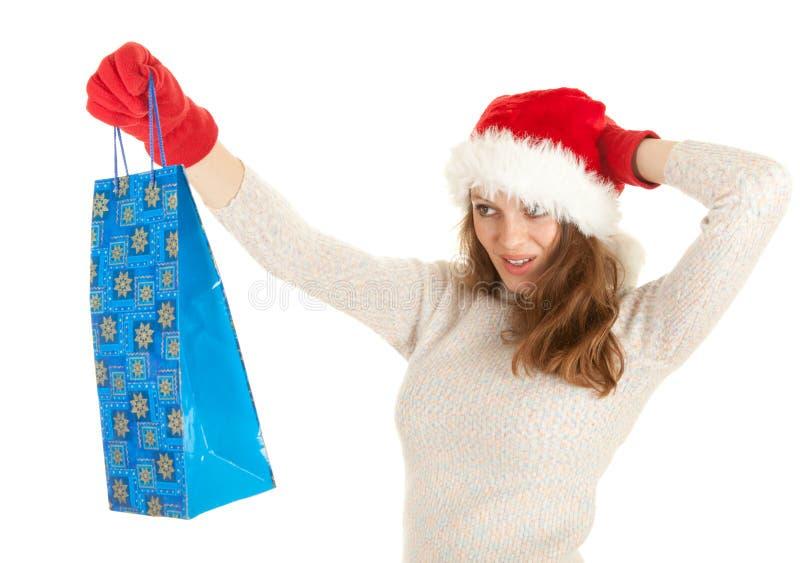 Het meisje kleedde zich in de hoed van de Kerstman dragende het winkelen zak royalty-vrije stock fotografie