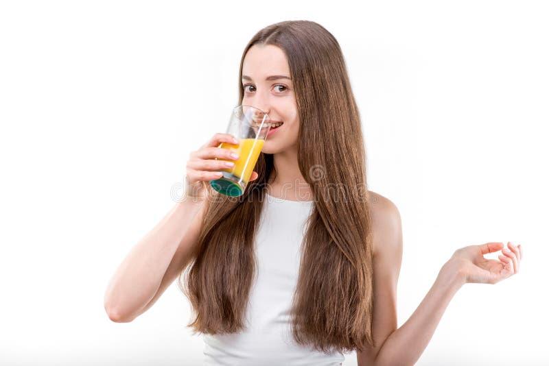 Het meisje kleedde zich in een wit overhemd het drinken jus d'orange stock fotografie