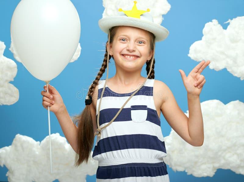 Het meisje kleedde zich in gestreepte kleding en hoed met ster het stellen op een blauwe achtergrond met katoenen wolken, witte l stock afbeeldingen