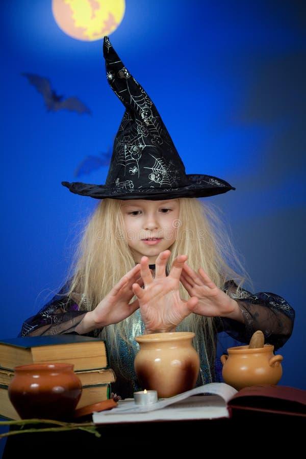 Het meisje kleedde zich omhoog als heks in nacht die magisch maakt royalty-vrije stock afbeelding