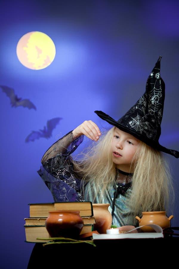 Het meisje kleedde zich omhoog als heks in nacht die magisch maakt royalty-vrije stock afbeeldingen