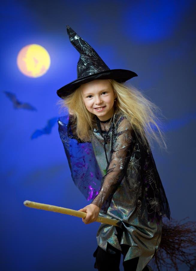 Het meisje kleedde zich omhoog als heks in nacht vliegende bezem stock fotografie