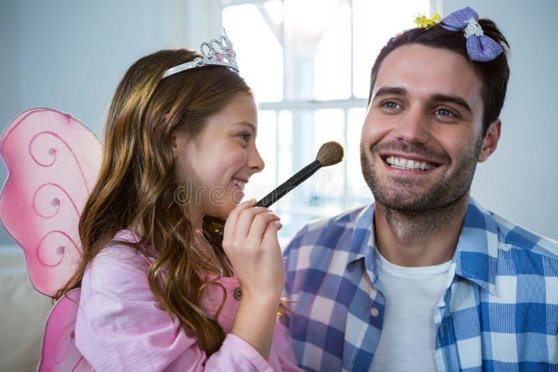 Het meisje kleedde zich omhoog in een feekostuum toepassend samenstelling op vadersgezicht royalty-vrije stock fotografie