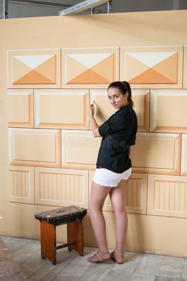 Het meisje kleedde zich in zwart-wit verfraaiend een muur royalty-vrije stock foto