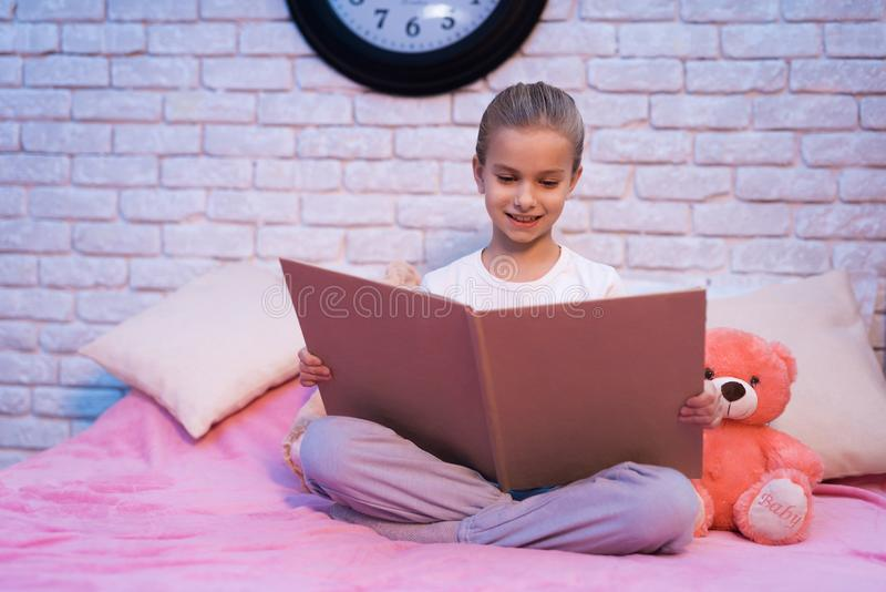 Het meisje, kleindochter leest thuis boek bij nacht stock fotografie