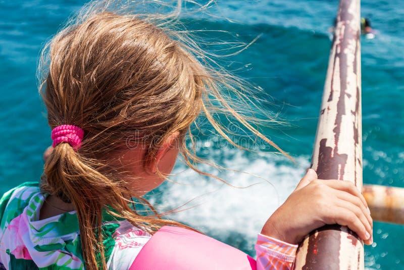 Het meisje in kleurrijke slijtage bekijkt het overzees, schietend van de rug royalty-vrije stock afbeeldingen