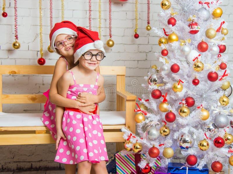 Het meisje koesterde terug haar zuster in het decor van het Nieuwjarenhuis stock foto