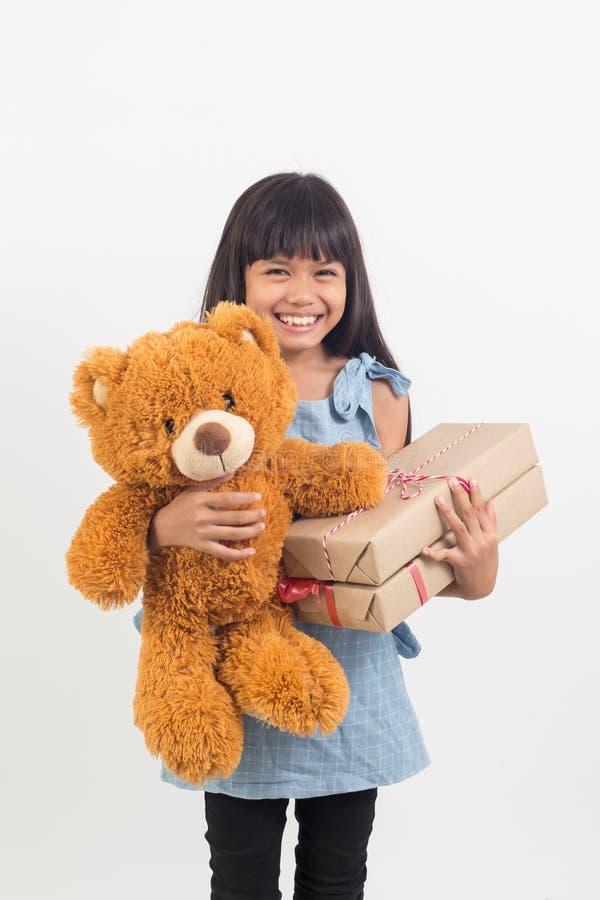 Het meisje koestert een teddybeer met giftdoos stock afbeeldingen