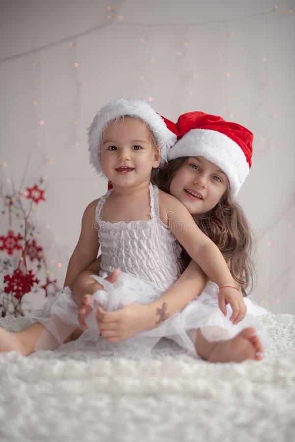 Het meisje koestert haar weinig zuster, allebei die rode Kerstmiskappen dragen en stock foto