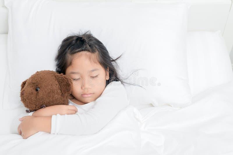 Het meisje koestert teddybeer terwijl het slapen in bed royalty-vrije stock fotografie