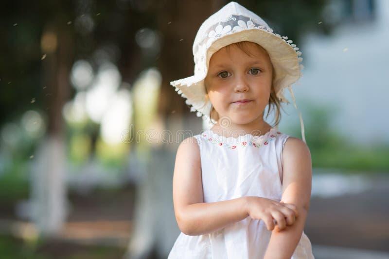 Het meisje krast haar hand van een mugbeet stock foto's