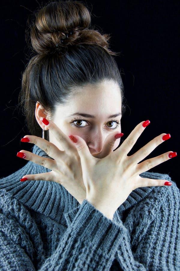 Het meisje kruist haar indient voorzijde van haar gezicht die spijkers tonen met royalty-vrije stock foto's