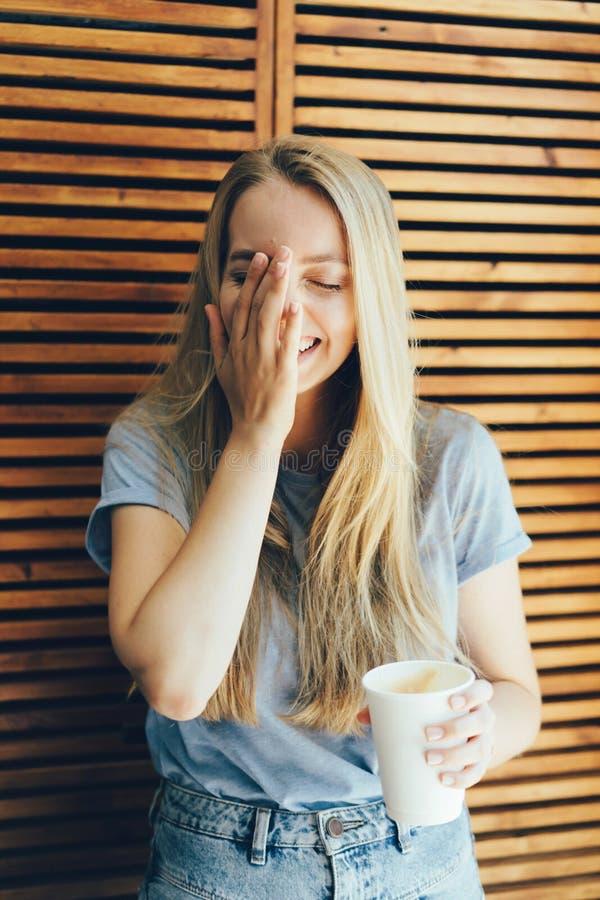 Het meisje lacht en behandelt haar gezicht met haar hand, natuurlijke emoties stock fotografie