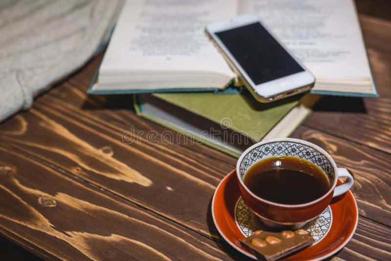 Het meisje leest het boek en heeft koffie Rust en lezingshuis stock afbeelding
