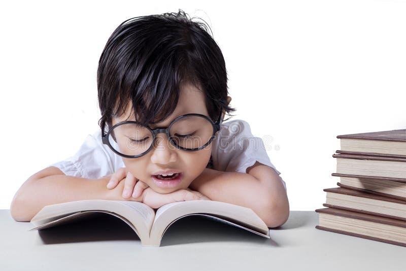 Het meisje leest handboek op bureau stock afbeeldingen