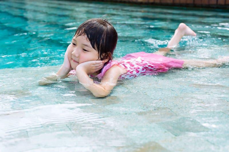 Het meisje legt op de pool stock foto