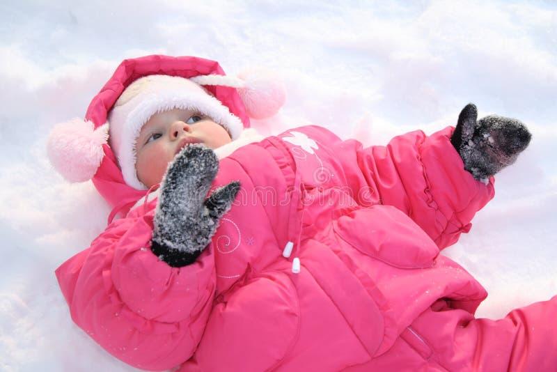 Het meisje legt op een sneeuw stock afbeelding