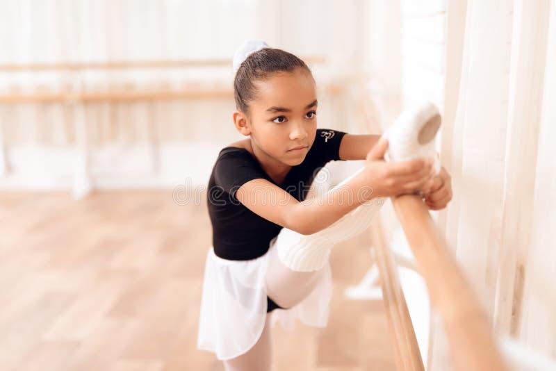 Het meisje leidt een rek van haar benen dichtbij het ballet op barr stock afbeelding