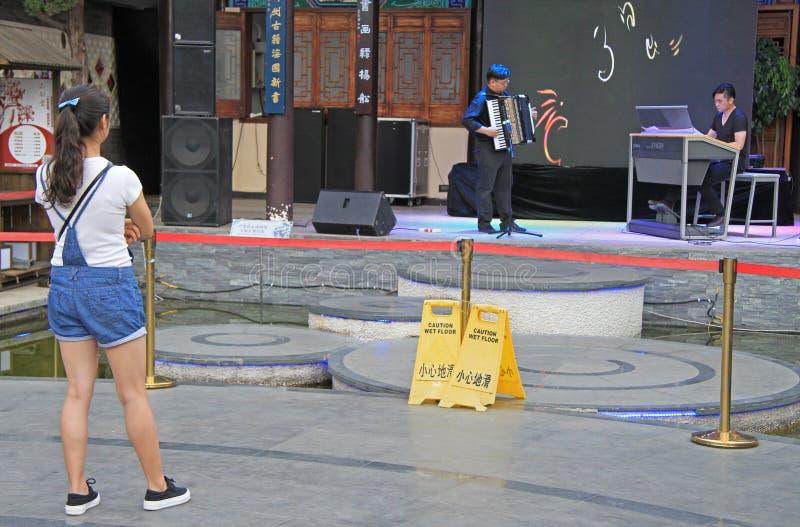 Het meisje let op prestaties in Kunming, China stock foto