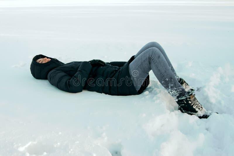 Het meisje ligt in de sneeuw stock fotografie
