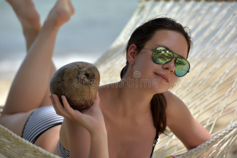 Het meisje ligt in een hangmat met een kokosnoot royalty-vrije stock foto's