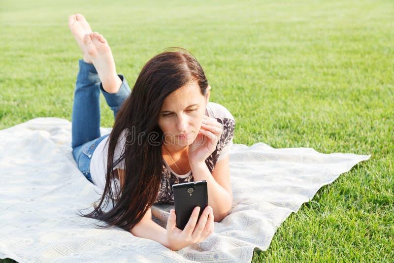 Het meisje ligt met telefoon stock foto