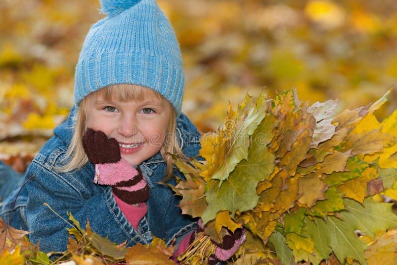 Het meisje ligt op de gele bladeren royalty-vrije stock foto