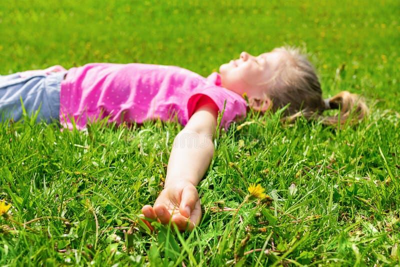 Het meisje ligt op de groene weide in vers gras Het concept van de zomer Selectieve nadruk De ruimte van het exemplaar Mening van royalty-vrije stock fotografie