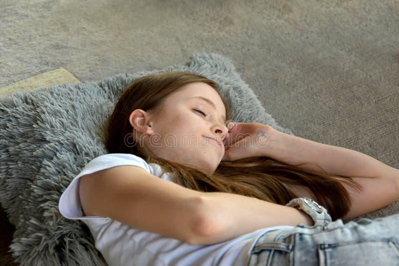 Het meisje ligt op de vloer stock foto's