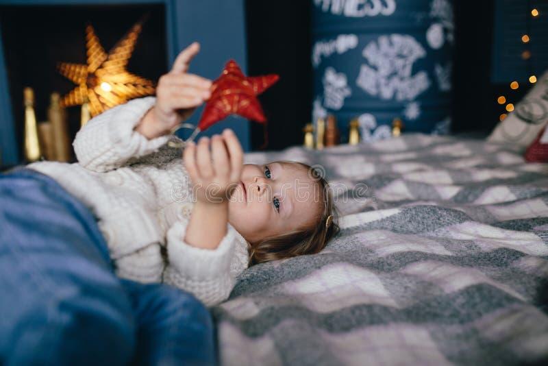 Het meisje ligt op een bed en een holding een rode ster, decoratie voor Kerstmis royalty-vrije stock afbeelding