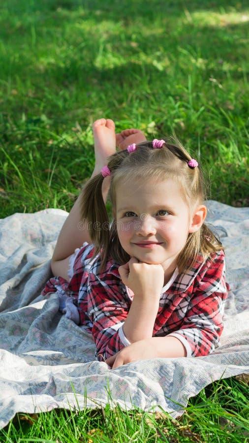 Het meisje ligt op een Mat op het gras stock afbeelding