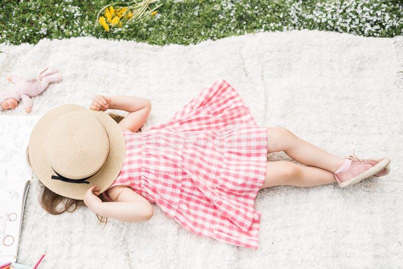 Het meisje ligt op een plaid met een hoed stock foto