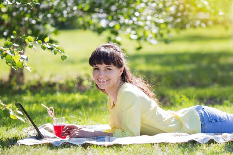 Het meisje ligt op het gras en houdt een glas sap stock foto