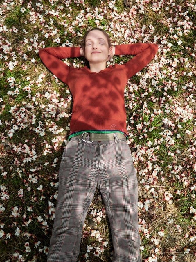 Het meisje ligt op het gras, met witte bloemen wordt behandeld die stock fotografie