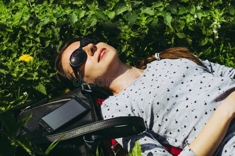 Het meisje ligt op het groene gras in zonnebril royalty-vrije stock afbeelding